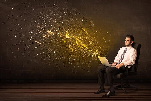 Businessman with laptop and energy explosion on background concept